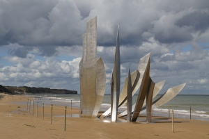 """Les Braves,"" a  nine-meter tall stainless steel sculpture by Anilore Ban rises from the sand at Omaha Beach near St. Laurent-sur-Mer, France. It honors all those men who landed here to liberate France. The sculpture has 3 elements: 1) Wings of Hope, 2) Rise, Freedom!, and 3) Wings of Fraternity."