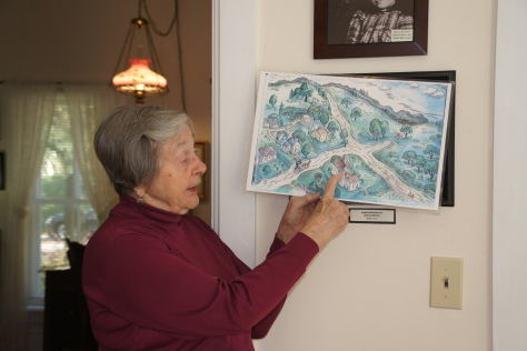 Docent Kathryn Hansen shows a Lois Lenski illustration of the Betsy-Tacy books and compares it to the neighborhood today.