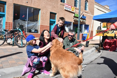 family patting golden retriever at Las Cruces Farmers Market www.offthebeatenpagetravel.com